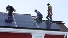 Editorial crews placing solar panels on a roof of a house Stock Footage