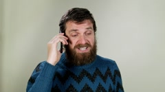 Angry hipster man at cellphone. Close up in studio on neutral background Stock Footage