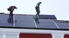 Editorial crews placing solar panels on the roof of a house Stock Footage