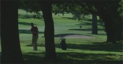 Golfer in the trees hit's out of the rough towards camera. Stock Footage