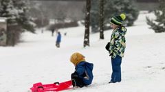 Two kids, boy brothers, sliding with bob in the snow, wintertime, happiness c - stock footage