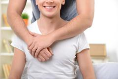 Loving homosexuals sitting on the sofa - stock photo