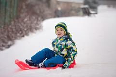 Two kids, boy brothers, sliding with bob in the snow, wintertime - stock photo