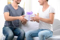 Pleasant guy giving present to his male partner - stock photo