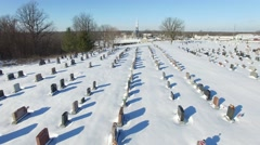 4k aerial flying in snowy graveyard with church background Stock Footage
