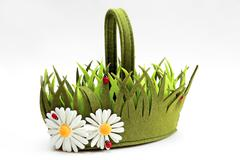 Decorative basket of felt in the form of grass and flowers Stock Photos