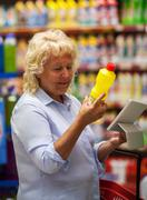 Senior woman with pad reading the detergent label - stock photo