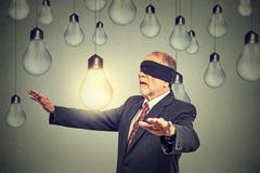 Blindfolded senior man walking through light bulbs searching for bright idea - stock photo