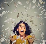 Happy woman exults pumping fists ecstatic celebrates success under a money ra Stock Photos