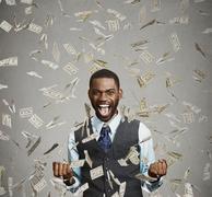 Happy man pumping fists ecstatic celebrates success screaming under money rai Stock Photos