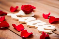 Stock Photo of close up of word love cutout with red rose on wood