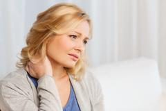 Unhappy woman suffering from neck pain at home Kuvituskuvat