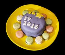 The title PF 2016 written on festive cake with handmade macaroons Stock Photos
