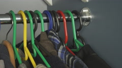 Clothes in the closet on hangers - stock footage