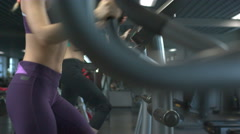 Slim fitness women exercising on a cross trainer, close up Stock Footage