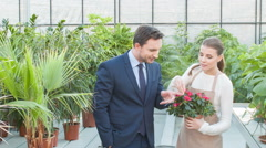 Florist shows particular flower to the manager - stock footage