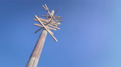 Low angle dolly shot vintage signpost several directions isolated blue sky Stock Footage