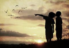 Two little friends on sunset standing and pointing at birds in the air Stock Photos
