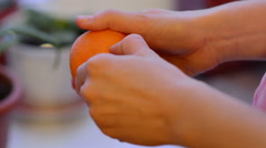 woman hands to peel fresh tangerine - stock footage