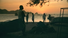 Fishermen on beach at sunset slow motion Stock Footage