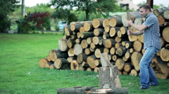Handsome man chopping wood in the garden Stock Footage