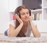 Happy Carefree Beautiful Young Woman, enjoyment in music on headphones at hom - stock photo