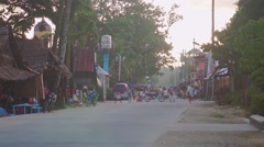 On a small street in a Filipino village people go and rides a motorcycle Stock Footage