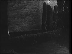 Rear view of woman in dressing gown tentatively walking into building, 1940s Stock Footage