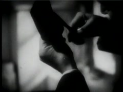 Medium shot of man creating female silhouette cameo out of paper, 1930s Stock Footage