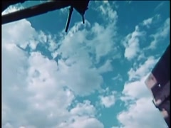 Low angle panning shot from clouds in blue sky to interior barn roof, 1970s Stock Footage
