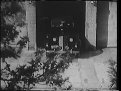 High angle shot of car driving out of garage, 1940s Stock Footage