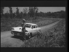 Three policemen stopping cars on country road, 1960s Stock Footage