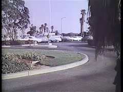 Wide shot of car on road pulling into driveway of house, Los Angeles, 1970s Stock Footage