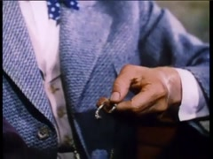 Medium shot of man rubbing his lucky horseshoe chain, 1950s - stock footage