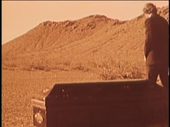 Man walking away from coffin in desert, 1970s - stock footage