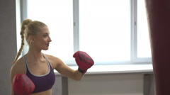 Beautiful young girl practicing Boxing in a gym, looking at the camera after the Stock Footage