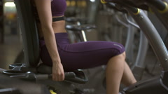 Young beautiful woman exercising on velosimulator Stock Footage