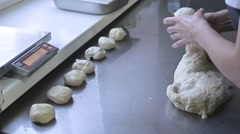 Baker divides the dough into portions and weights them Stock Footage