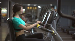 Young beautiful woman exercising on velosimulator talking with instructor Stock Footage