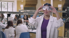 Student in a science lab putting on safety goggles and smiling Stock Footage