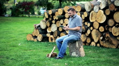 Young man with tablet standing close to the stumps in homestead Stock Footage