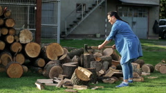 Man teach his wife chopping wood in the homestead Stock Footage