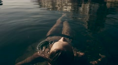 Beautiful model lying on the surface of the sea Stock Footage