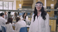 Student in a science lab wearing safety goggles and smiling Stock Footage