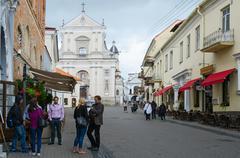 Tourists on street Ausros Vartai near church of St. Theresa - stock photo