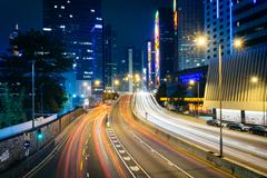Long exposure of traffic on Connaught Road and skyscrapers at night, in Hong  - stock photo