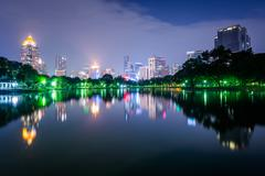 Lake and skyscrapers at night, at Lumphini Park, in Bangkok, Thailand. - stock photo