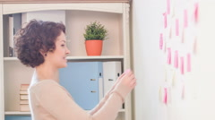 Coworkers are attaching post-it notes to the wall Stock Footage