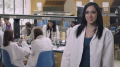 Student in a science lab crossing her arms and smiling Stock Footage
