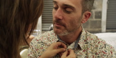 Stock Video Footage of Woman closing her husband's collar button while talking in cafe